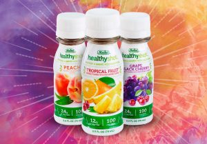 Three healthyshot high protein bottles overtop a color background